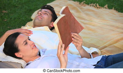 Couple relaxing outdoors - Woman reading a book to her...