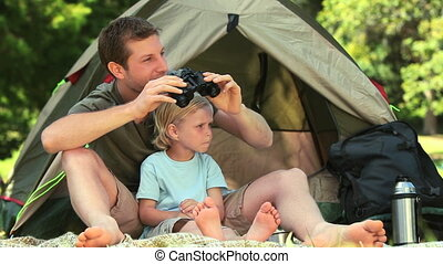 Father and son using binoculars to look at something outside...