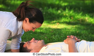 Woman laughing with her boyfriend while lying on the grass...