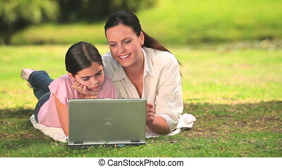 Woman and daughter using a laptop - Mother and young...