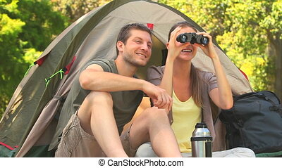 Couple camping in the country side - Couple sitting outside...