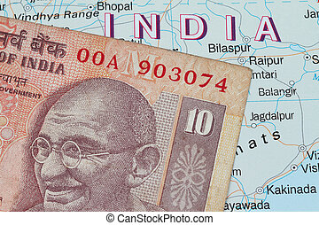 Indian currency - Indian rupees against the outline of India...