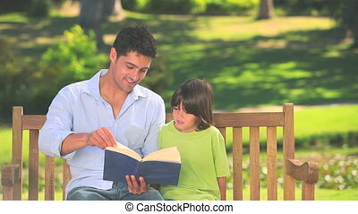 Man reading a book with his son