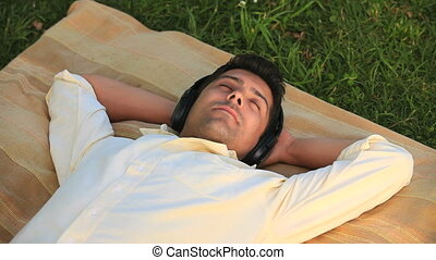 Man listening to music outdoors - Man lying rexaxing on the...