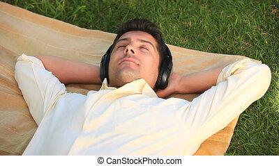 Man relaxing listening to music - Man lying relaxing...
