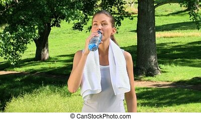 Young woman drinking water after sports