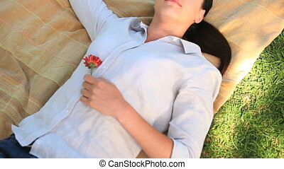 Woman lying outdoors holding a rose - Woman lying on a rug...