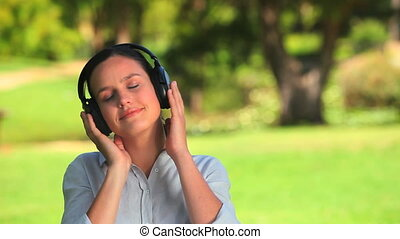 Young woman listening to music - Dark-haired woman enjoying...