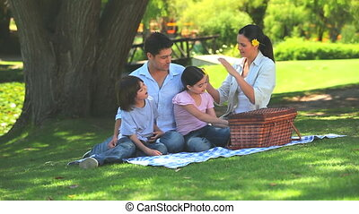 Happy family eating watermelon while picnicking under a tree...
