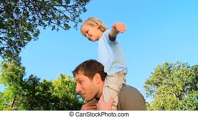Father carrying his son - Father carrying his happy son on...