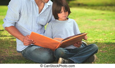 Father and son reading outdooors
