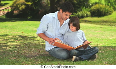 Cute little boy with his father looking at an album sitting...