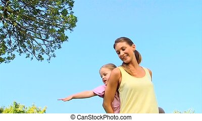 Woman with her daughter on her back