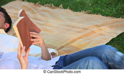 Couple having rest - Man sleeping on a rug outdoors while...
