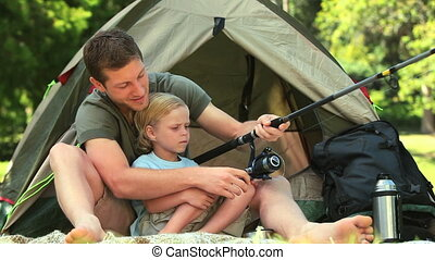 Father teaching his son how to fish - Father showing his son...