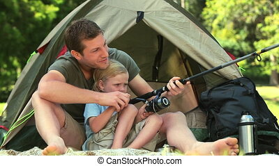 Little boy learning to fish - Father teaching his son how to...