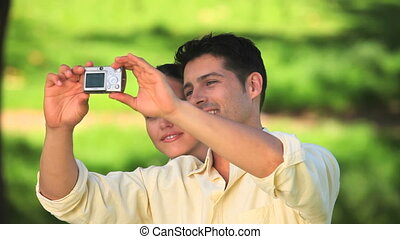 Couple taking pictures of themselves outdoors