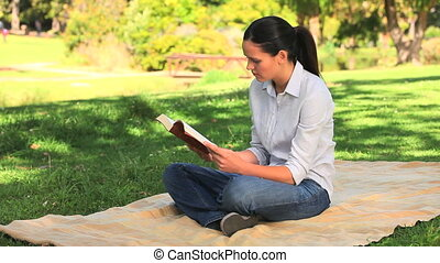Woman reading a book while sitting on a rug under a tree