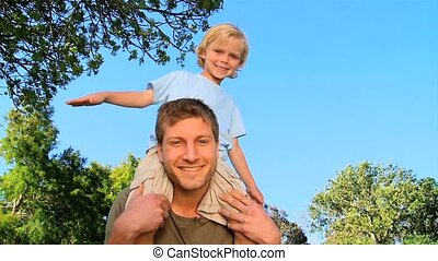 Father with his son on shoulders - Father carrying his son...