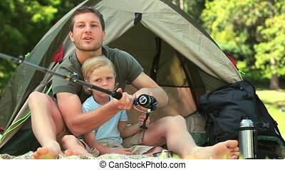 Little boy learning how to fish - Father showing his little...