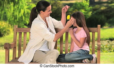 Mom and daughter playing withflower