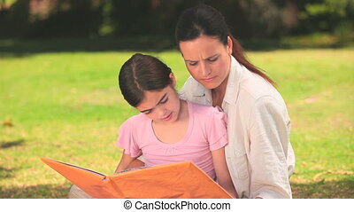 Mother and daughter reading outdoor - Mother and her...