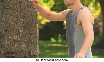 Sportsman leaning against a tree to take a rest after...
