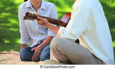 Couple sitting playing guitar - Attractive man playing...