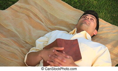 Handsome man sleeping outdoors - Handsome man sleeping with...