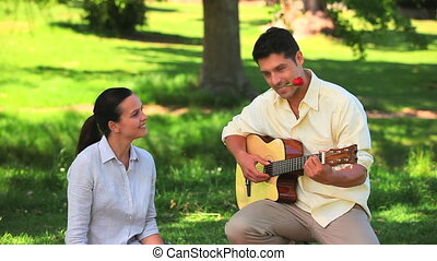 Man playing guitar with a rose between his teeth sitting...