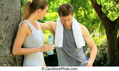 Athletic couple having a drink of w