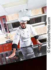 chef washing kitchen counter - young male chef washing...