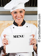 chef holding menu - young female chef holding a white board...