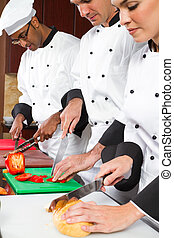 chefs cooking - group of professional chefs cooking in...