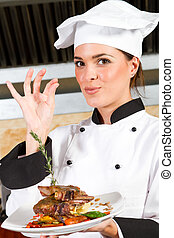 female chef presenting food - young beautiful female chef...