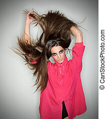 Young brunette lady dressed in pink blouse playing with long hairs, ring flash studio portrait on white