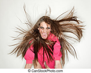 Screaming furious aggressive brunette lady with flying long hairs, ring flash studio portrait on white