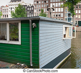 houseboat with open windows in amsterdam canal.
