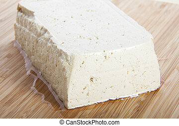 Tofu - Block of fresh tofu on cutting block.