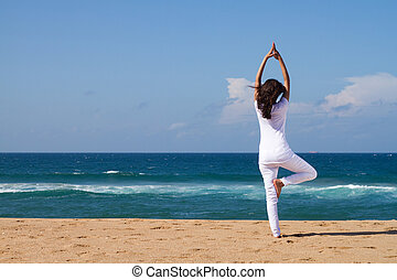 yoga - young woman doing yoga on beach