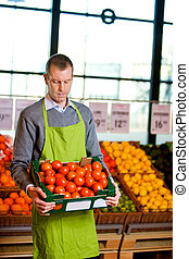 Grocer with Tomatoes - A male grocery owner with a box of...