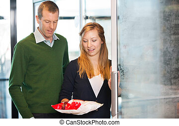 Couple Buying Frozen Food - Woman taking out product from...