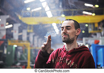 industry worker smoke cigarette at job in company at big...