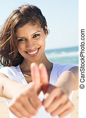 happy young woman giving thumbs up hand sign on beach
