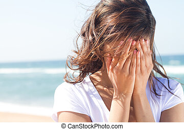 young woman cover her face with hands on beach