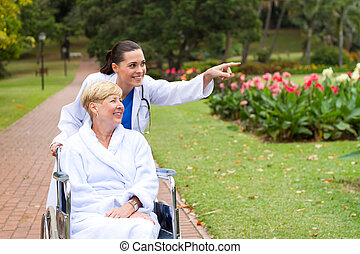 caring nurse and disable patient - female nurse taking...