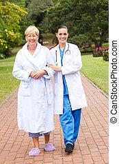 nurse taking senior patient outdoor - caring doctor or nurse...