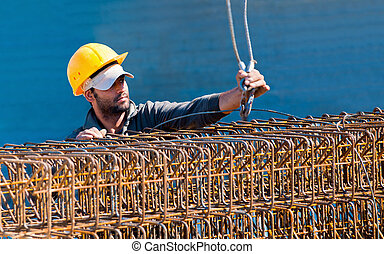 Authentic construction worker loading steel reinforcement stirrup beam cages to a crane hook