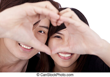 Happy couple forming heart by touching hands together