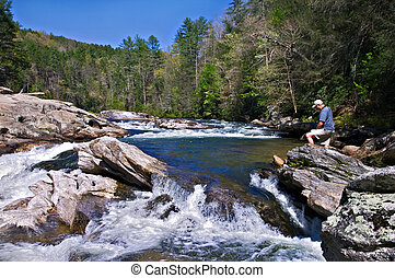 Man on Rocks at River - Man standing on the rocks at the...
